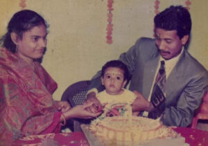 Rosalinee as baby cutting cake with her parents